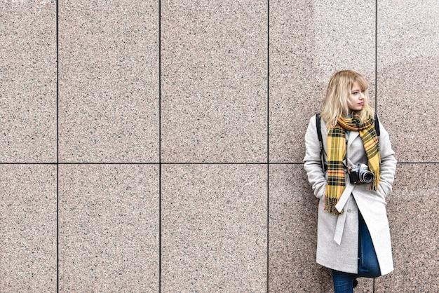 Een blonde vrouw met een retro camera staat tegen de muur en kijkt weg. vrije ruimte. kopieer ruimte
