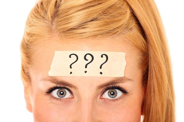 Een blonde vrouw met een tape op haar voorhoofd en drie vraagtekens erop