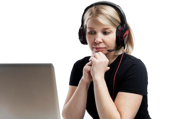 Een blonde vrouw met koptelefoon en een microfoon zit aan een tafel met een laptop