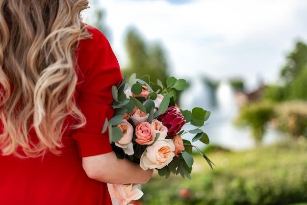 Een blonde vrouw met krullend haar houdt een mooi gekleurd boeket in haar handen,