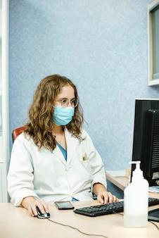 Een blonde vrouwelijke arts met bril en gezichtsmasker werkt op haar computer op haar kantoor.