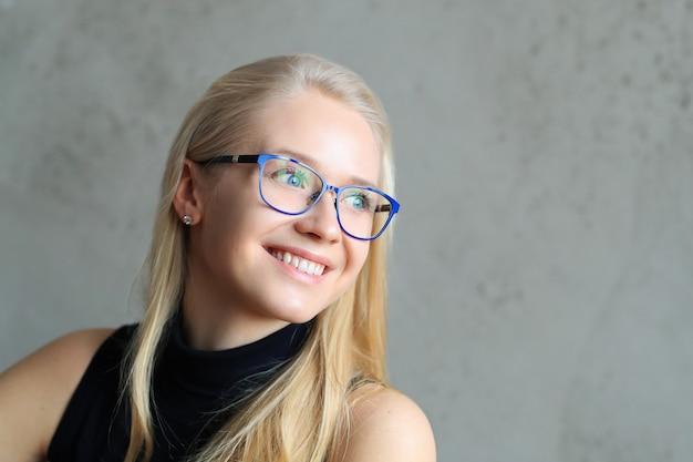 Een blonde zakelijke ladu in blauw montuur brillen