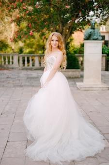 Een blondharige bruid in een weelderige witte jurk staat op de plek bij de oude kerk in prcanj