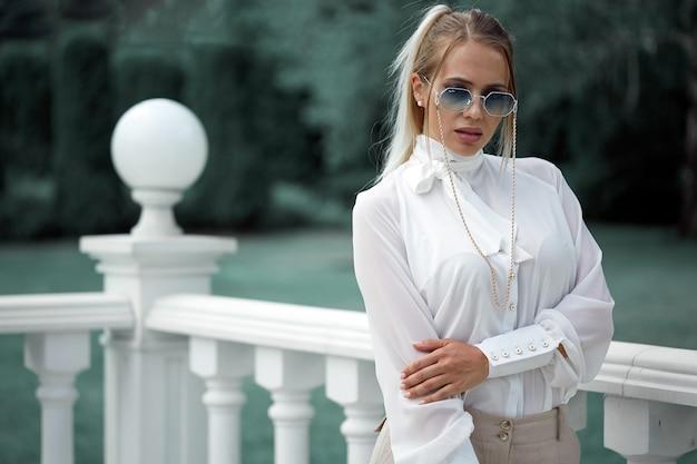 Een blondine in een witte blouse en zonnebril poseert tegen de achtergrond van balusters en een tuin