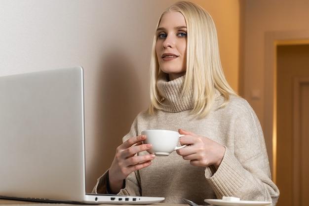 Een blondine met blauwe ogen in een beige trui met een brede kraag zit achter de computer met een witte mok thee