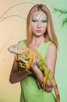 Een blondje op een zachte manier met een wild roofdier in haar handen. leguaan in gevangenschap