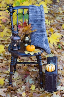 Een boek, een pompoen, een gebreide sjaal, een oude lantaarn en een oude koffer ernaast