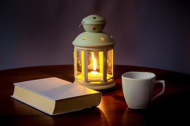 Een boek en een kopje koffie in het licht van een lantaarn met 's avonds een kaars