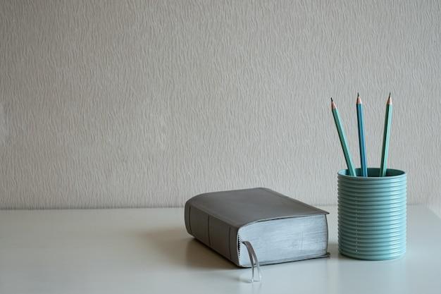 Een boek en pastelpotloden in het blauwe glas op het bureau bij grijze muurachtergrond