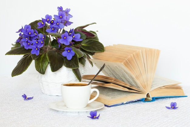 Een boek met een kopje koffie op een witte tafel en bloemen in een mand.
