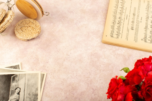 Een boek met muzieknoten van bovenaf wordt geopend, samen met rode rozenchips en foto's op roze