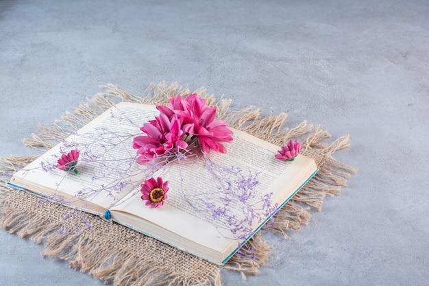 Een boek met paarse bloemen op zak