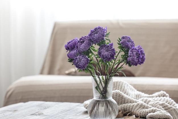 Een boeket blauwe chrysanten in een glazen vaas op de tafel in het interieur van de kamer.