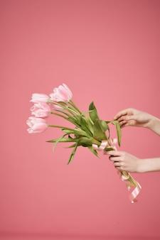 Een boeket bloemen in de hand en een cadeau romantiek zomer roze achtergrond