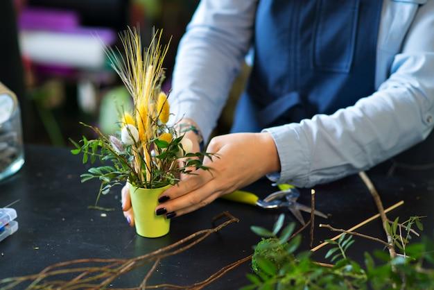 Een boeket bloemen in de handen van een bloemist