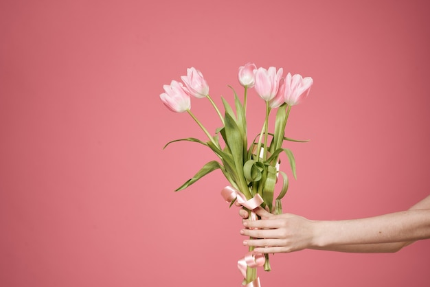 Een boeket bloemen in de handen van een roze vrouwenmuur.
