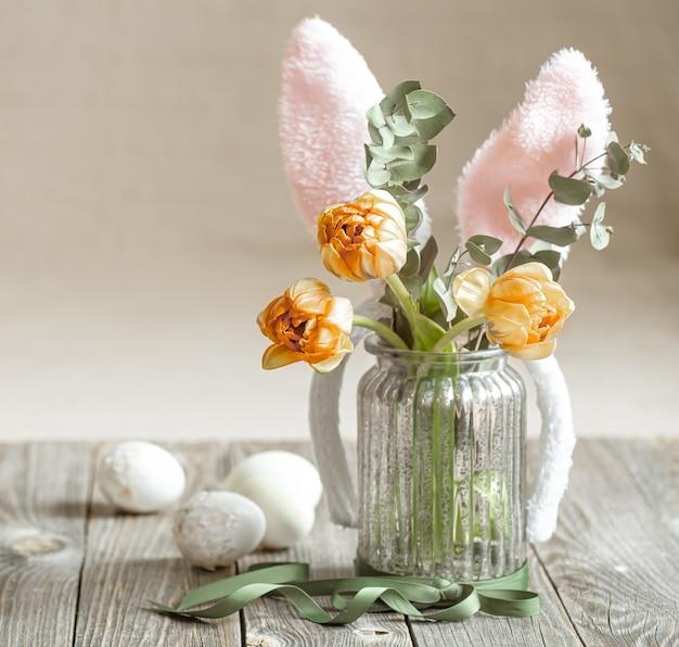 Een boeket bloemen in een glazen vaas met decoratieve elementen. pasen vakantie concept.