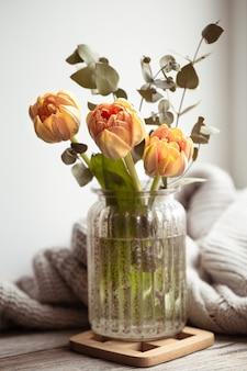 Een boeket bloemen in een glazen vaas op een onscherpe achtergrond.