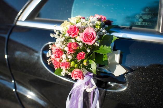 Een boeket bloemen op een autodeur