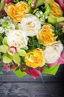 Een boeket bloemen op een donkere houten achtergrond. boeket met rozen.