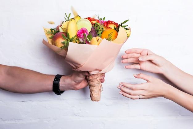 Een boeket fruit en bloemen wordt gegeven door een man