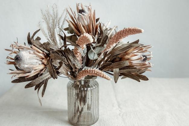 Een boeket gedroogde bloemen in een glazen vaas op een lichte achtergrond.