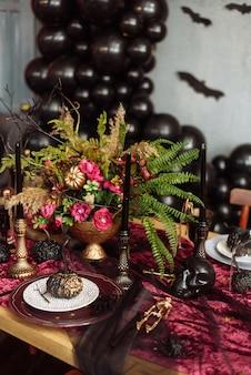 Een boeket gedroogde bloemen op tafel ter ere van halloween. een vleermuis op een serveertafel.