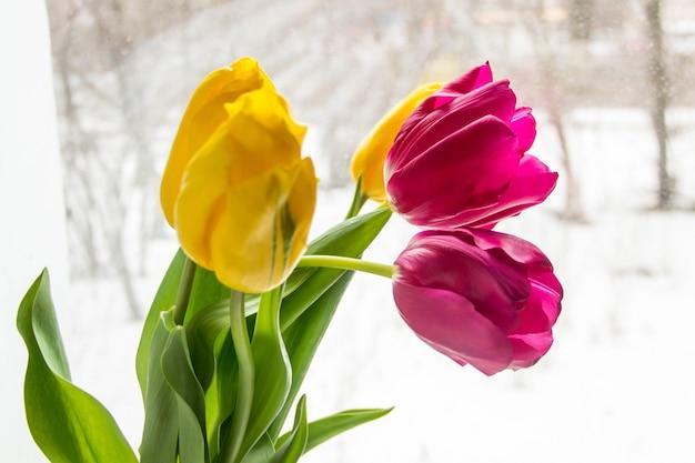 Een boeket gele en roze tulpen in een vaas op de vensterbank.