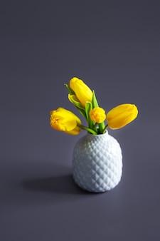 Een boeket gele tulpen in een vaas. minimalisme op een pastel achtergrond