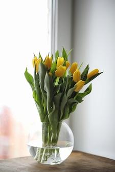 Een boeket gele tulpen in een vaas op de vensterbank. een cadeau voor een vrouwendag van gele tulpenbloemen. mooie gele bloemen in een vaas bij het raam.