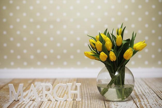 Een boeket gele tulpen in een vaas op de vloer. een cadeau voor een vrouwendag van gele tulpenbloemen. mooie gele bloemen in een vaas aan de muur.