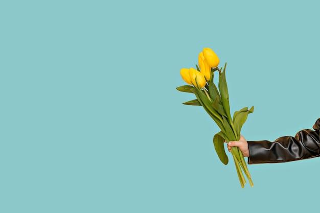Een boeket gele tulpen in je hand