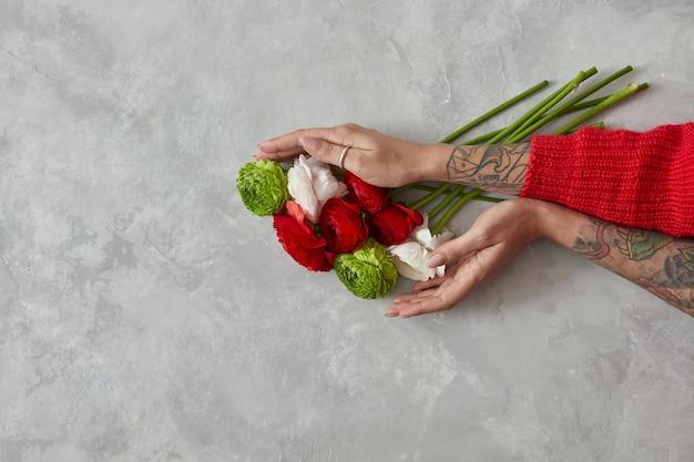 Een boeket gemaakt van verschillende bloemen, het meisje houdt in handen op een grijze betonnen achtergrond. bovenaanzicht