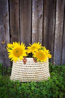 Een boeket grote zonnebloemen in een strozak staat bij een houten huis.