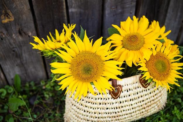 Een boeket grote zonnebloemen in een strozak staat bij een houten oud huis.