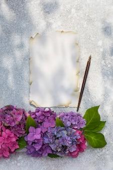 Een boeket hortensia's, een vel papier en een vulpen