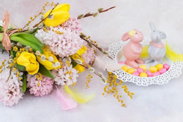 Een boeket hyacinten en tulpen, twee figuren van konijnen