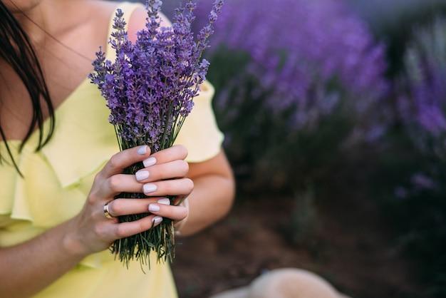 Een boeket lavendel in de handen van een meisje in een gele jurk