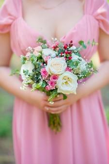 Een boeket levende bloemen in de handen van nesta in een roze jurk