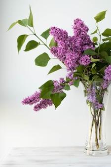 Een boeket lila bloemen in een transparante vaas, een boeket lente lila bloemen