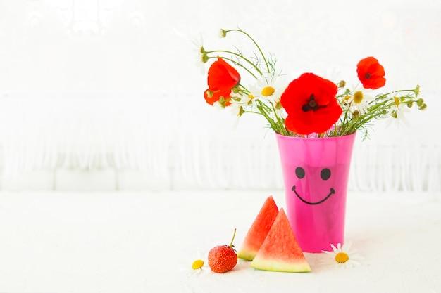 Een boeket madeliefjes en klaprozen in een roze vaas met een beschilderde snuit, aardbeien en watermeloenschijfjes op de tafel bij het raam.