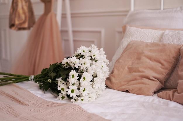 Een boeket madeliefjes op een bed in de scandinavische stijl van een slaapkamer