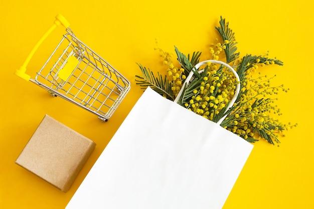 Een boeket mimosa in een witte mock-up papieren zak, een geschenkdoos en een kruidenierskar.
