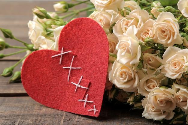 Een boeket mooie tedere mini rozen op een bruin houten tafel met hartjes