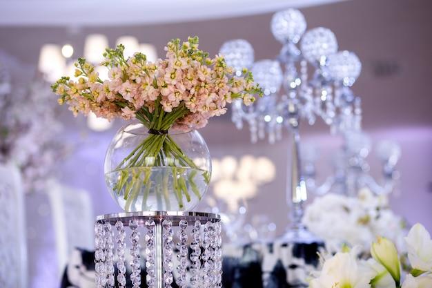 Een boeket prachtige perzikbloemen op een groene stengel in een ronde vaas op een kristallen standaard in het concept bruiloftsdecor. lente bloemen. floristiek, decoratie van het interieur met verse bloemen