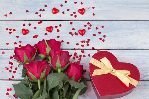 Een boeket rode rozen en een geschenk in een doos