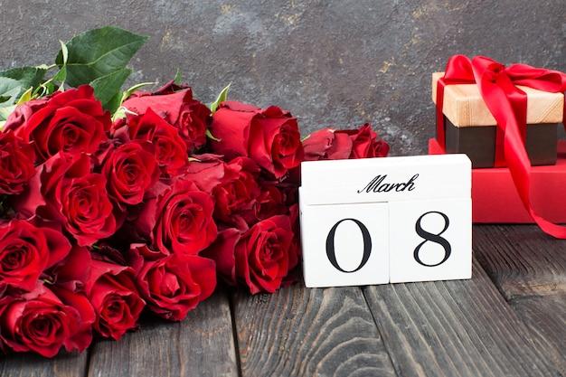Een boeket rode rozen, geschenken in een doos en de datum van 8 maart