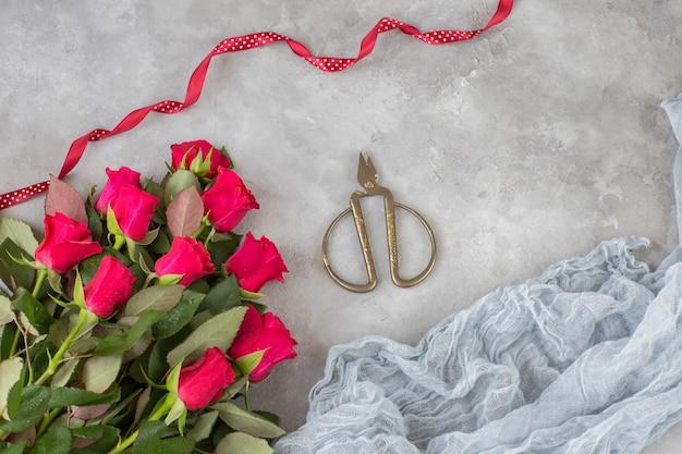 Een boeket rode rozen, oude schaar, een rood lint en gaas
