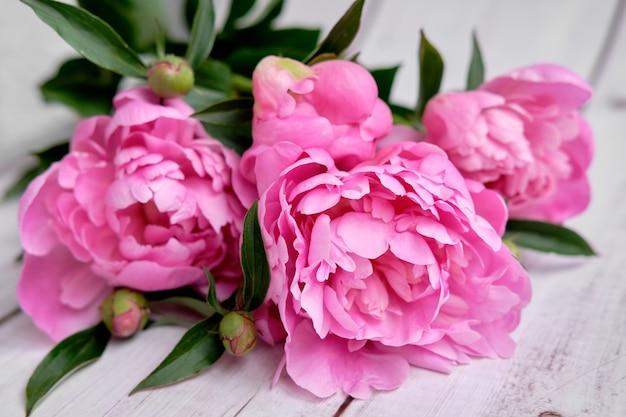 Een boeket roze karmozijnrode pioenrozen ligt close-up op een houten tafel