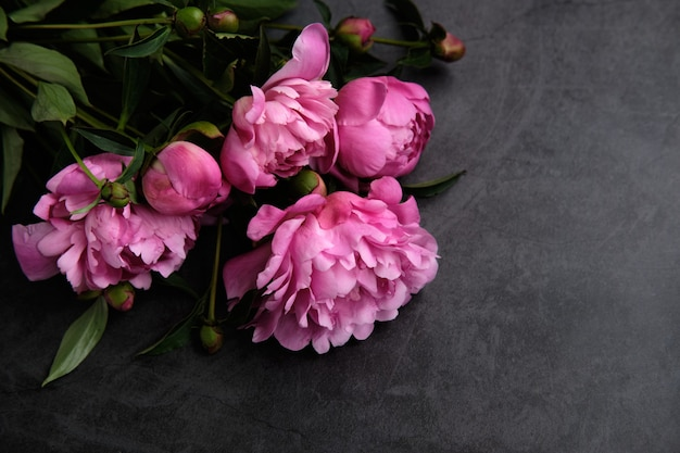 Een boeket roze pioenrozen op een donkere achtergrond